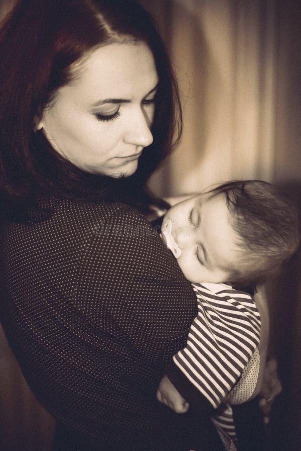 Le bébé est tombé endormi dans des mains du ` s de mère photos libres de droits