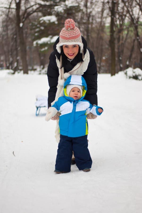 Le bébé font des premières étapes dans la neige photos stock