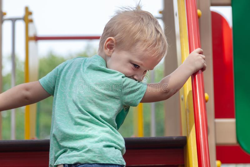 Le bébé garçon blond caucasien mignon drôle joue sur le terrain de jeu, s'élevant à upstair images libres de droits