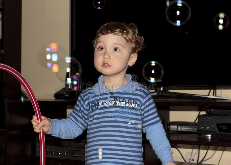 Le bébé garçon contemple des bulles de savon photo libre de droits