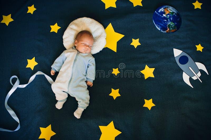 Le bébé garçon est endormi et se rêve un astronaute dans l'espace images stock