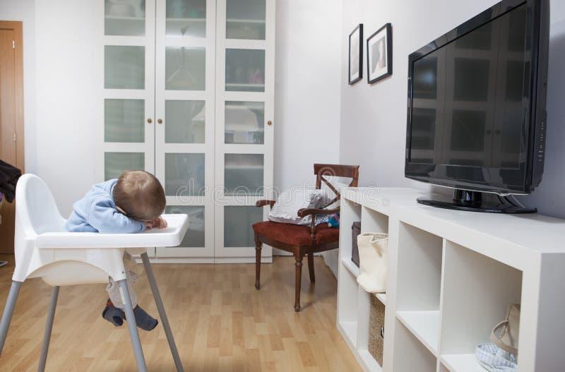 Le bébé garçon est tombé endormi sur son highchair images stock