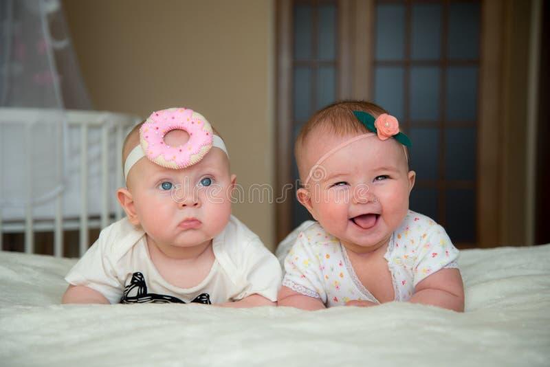 Le bébé garçon et la fille jumeaux se trouvent sur le lit photo libre de droits