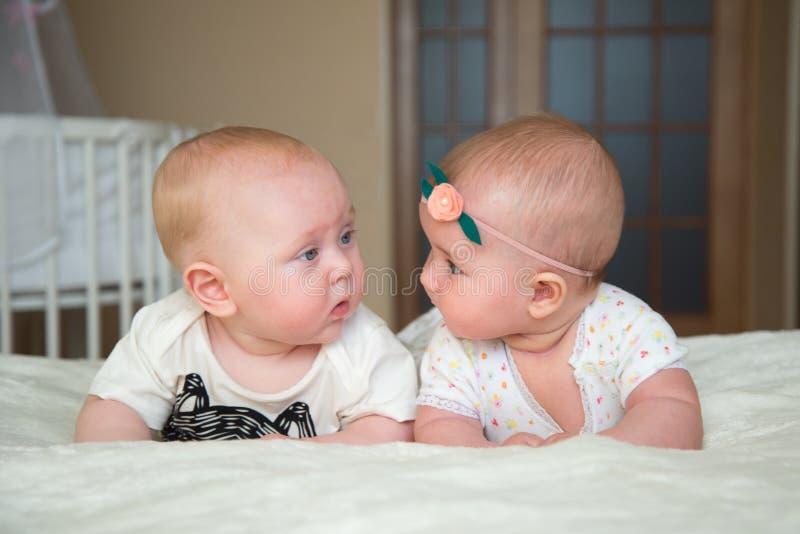 Le bébé garçon et la fille jumeaux se trouvent sur le lit photos libres de droits