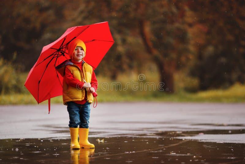 Le bébé garçon heureux d'enfant avec les bottes en caoutchouc et le parapluie sautent dans le pudd photo stock