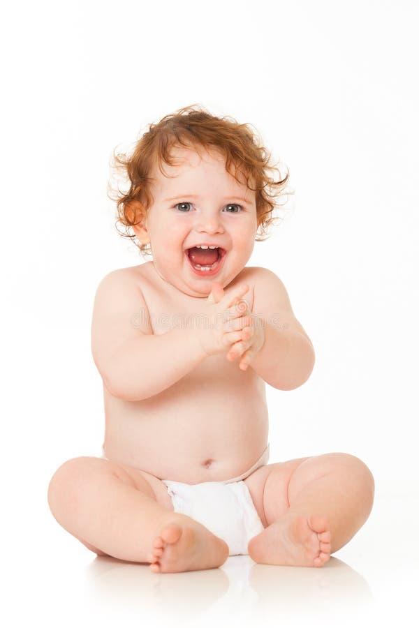 Le bébé garçon heureux s'assied sur le blanc images stock