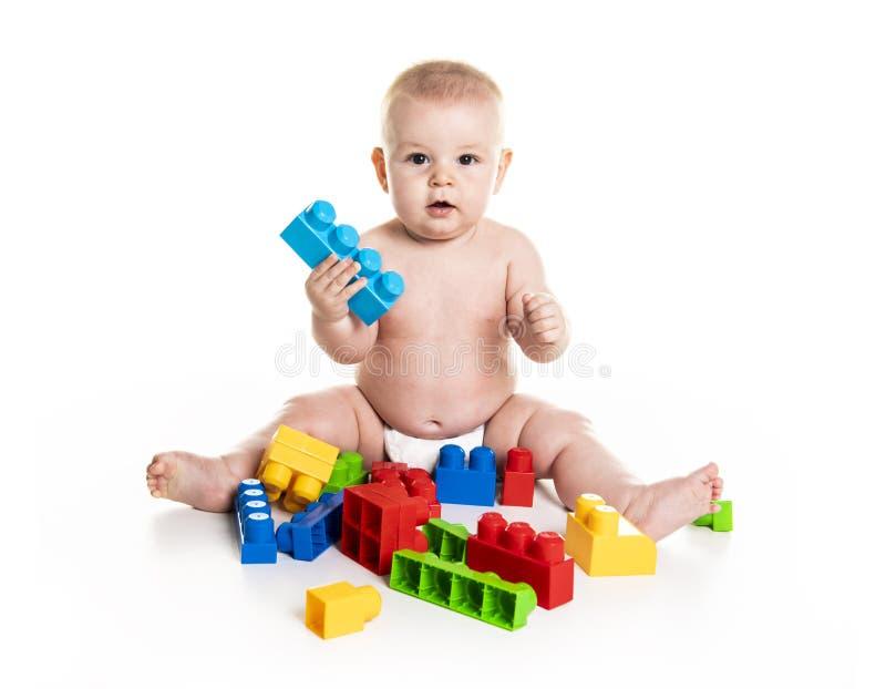 Le bébé garçon joue avec des blocs de jouet au-dessus du fond blanc photo libre de droits