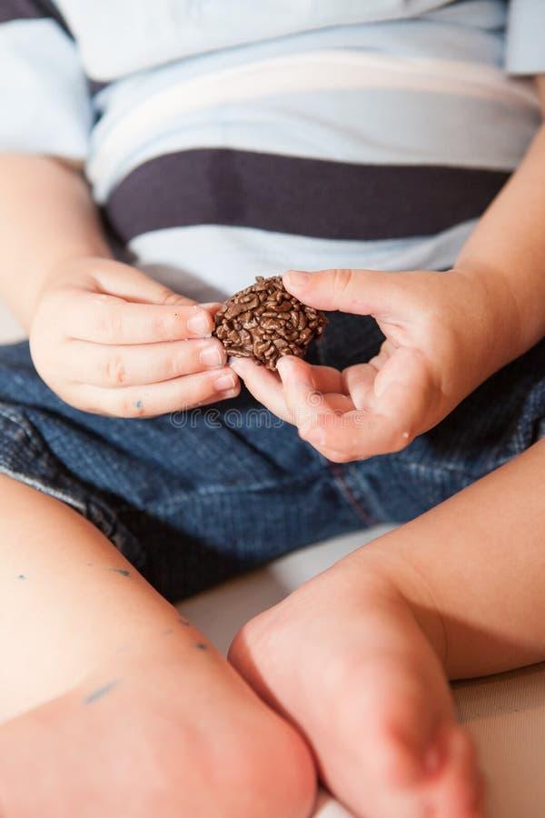 Le bébé garçon mange de petits bonbons au chocolat photo libre de droits