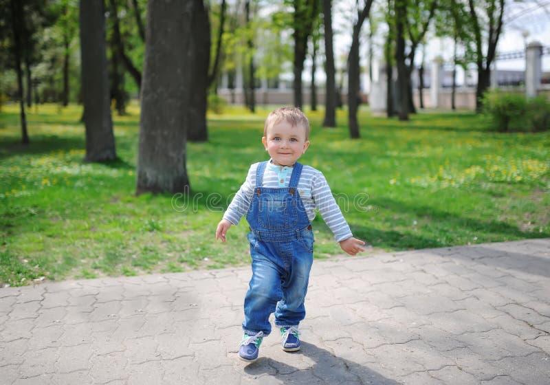 Le bébé garçon mignon avec le sourire doux, supports dans une pose drôle dans la ville verte garent la nature image stock