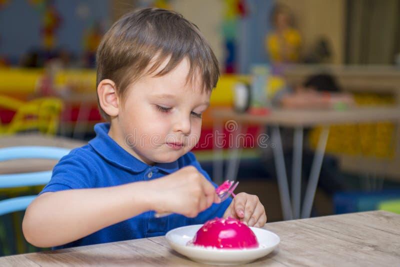 Le bébé garçon mignon mangent du pain grillé de miel dans le restaurant Peu d'enfant mange des butées toriques L'enfant mange dan photo libre de droits