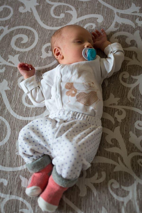 Le bébé garçon nouveau-né se trouve sur le lit suçant une tétine et des sommeils L'homme était né Vie de famille image libre de droits