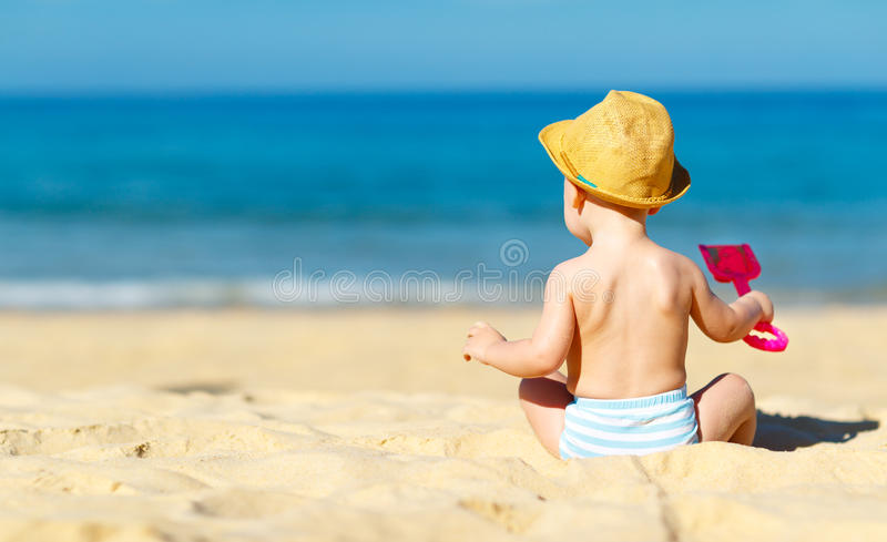 Le bébé garçon s'asseyent de retour avec des jouets sur la plage photographie stock