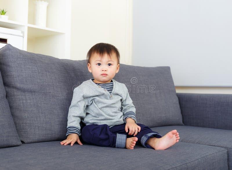 Le bébé garçon s'asseyent sur le sofa images stock