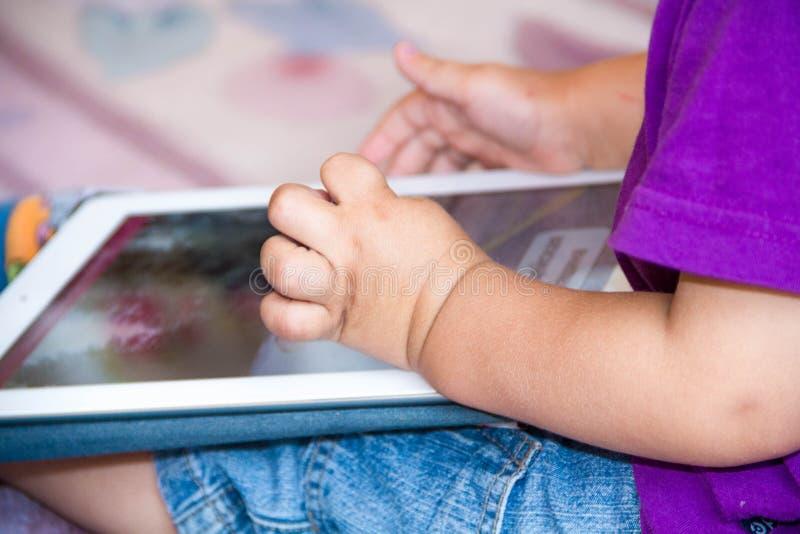 Le bébé garçon s'assied sur le plancher jouant avec le PC de comprimé Photo en gros plan des mains Peu de pavé tactile, apprenant images libres de droits