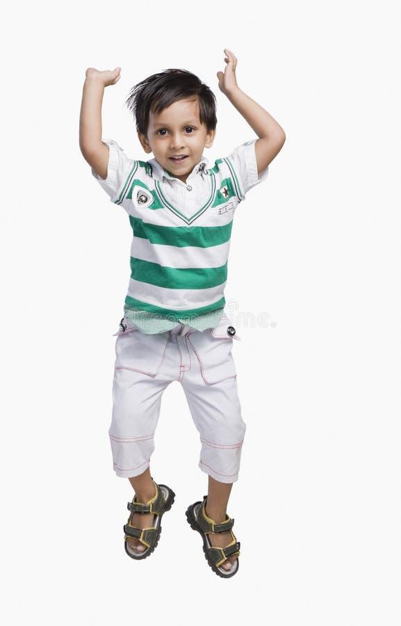 Le bébé garçon sautant et souriant image stock