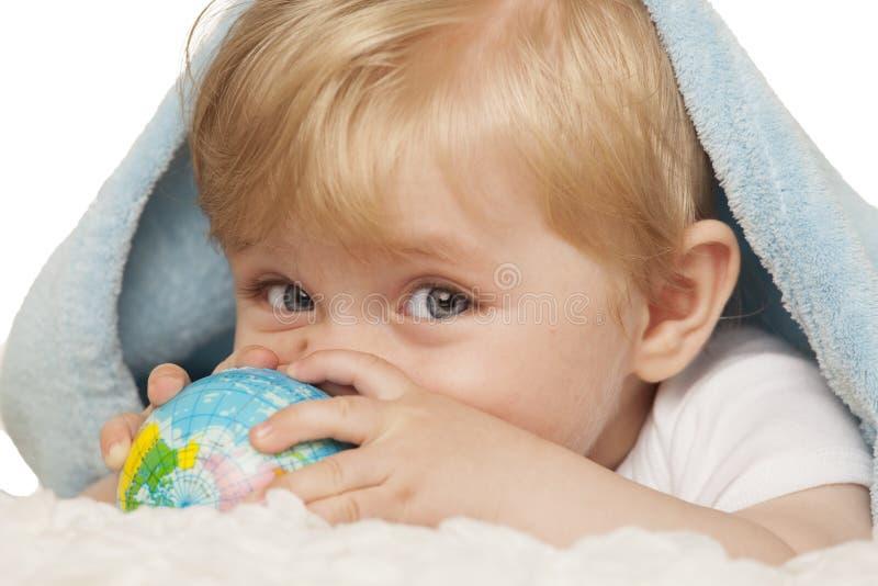 Le bébé garçon tient le petit globe dans des ses mains images libres de droits