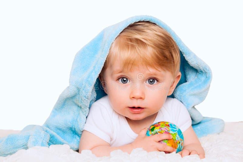 Le bébé garçon tient le petit globe dans des ses mains D'isolement sur un CCB blanc images stock