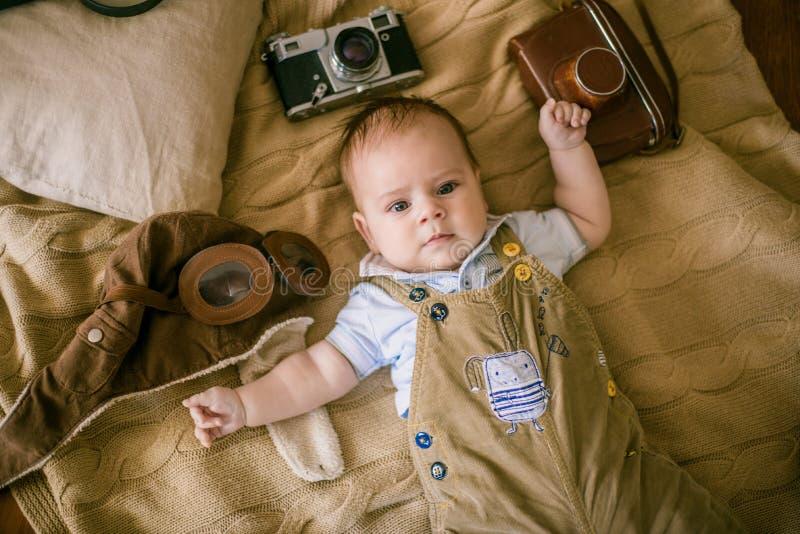 Le bébé heureux se trouve sur une couverture de maison avec des livres, un rétro appareil-photo et un casque pilote du ` s à la m photographie stock