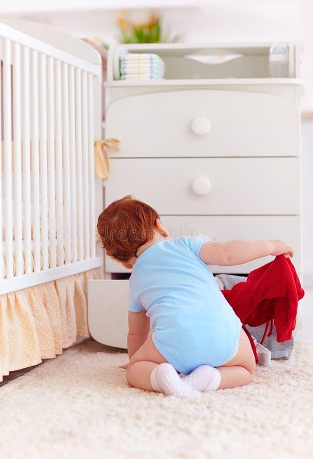 Le bébé infantile drôle jetant vêtx de la raboteuse à la maison image stock