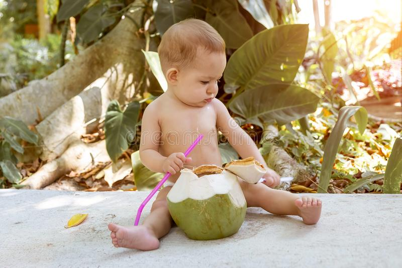 Le bébé infantile songeur et passionné s'assied au sol et mange et boit la jeune noix de coco verte avec la cuillère et la paille photos stock