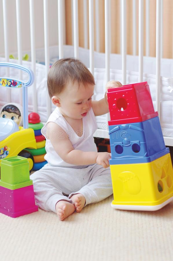 Le bébé joue des blocs d'emboîtement à la maison photos libres de droits