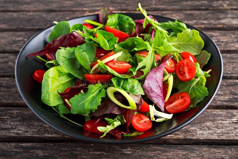 Le bébé laisse la salade avec des tomates-cerises et des anneaux de poireau photographie stock