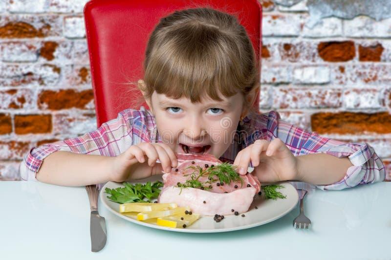 le bébé mange d'un bifteck photos libres de droits