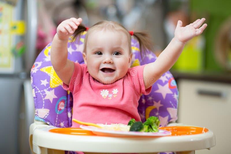Le bébé mange des pâtes se reposant dans le highchair dans la cuisine photographie stock