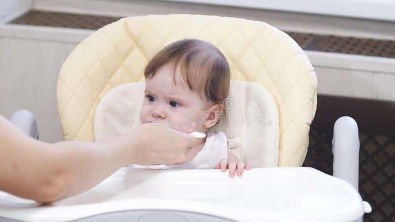 Le bébé mange du gruau de la cuillère, crache et sourit se reposant sur le highchair dans la cuisine images stock