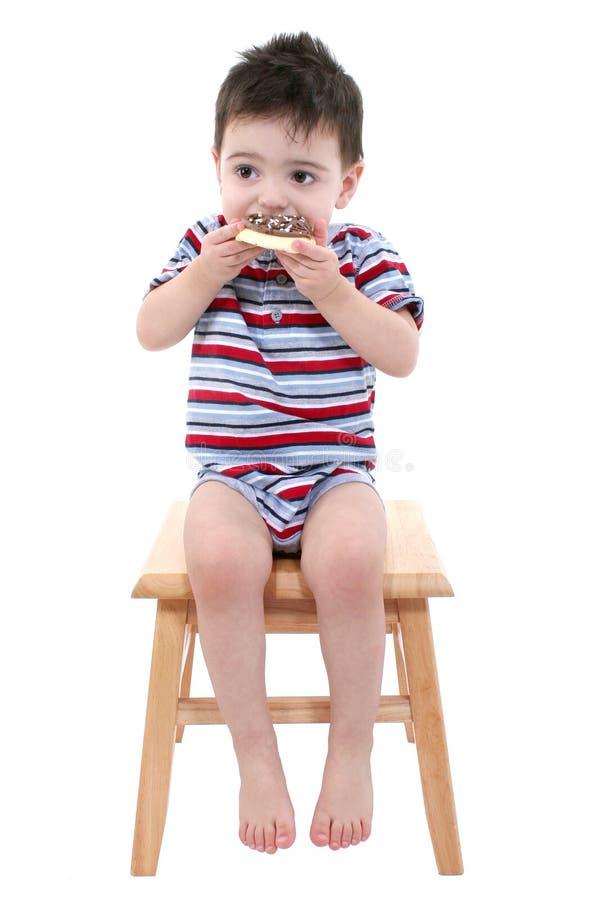 Le bébé mangeant du chocolat a glacé le biscuit de sucre au-dessus du blanc images libres de droits