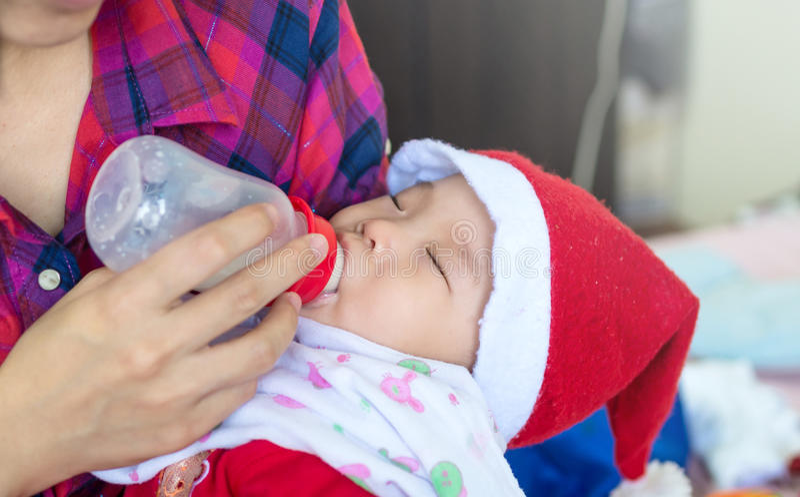 Le bébé mangeant du lait de la bouteille sur la mère alimente son Bab nouveau-né photos libres de droits