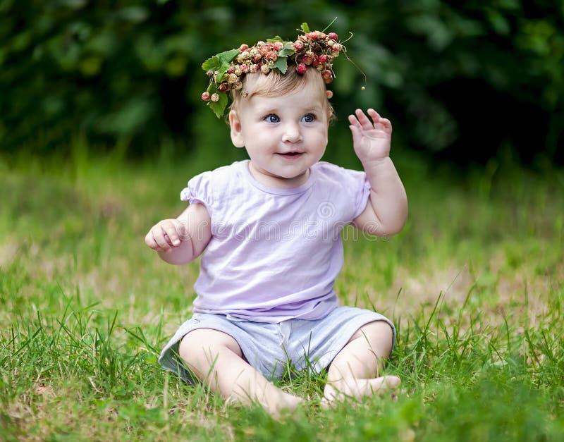 Le bébé mignon avec des cheveux d'or et le fraisier commun couronnent photos stock