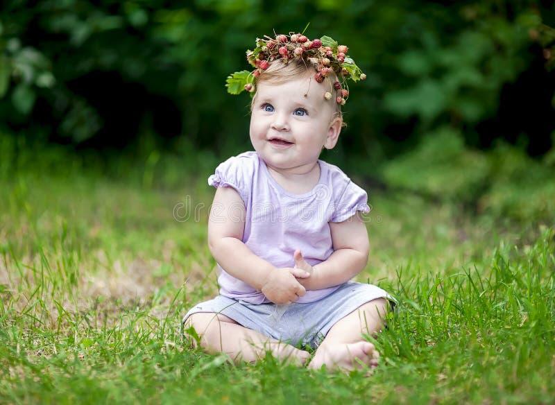 Le bébé mignon avec des cheveux d'or et le fraisier commun couronnent images libres de droits