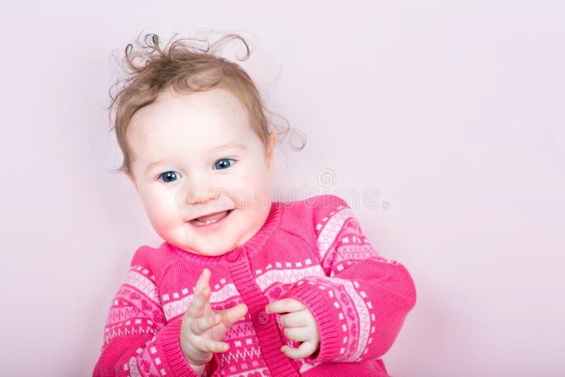 Le bébé mignon dans un rose a tricoté le chandail avec le modèle de coeurs photos libres de droits