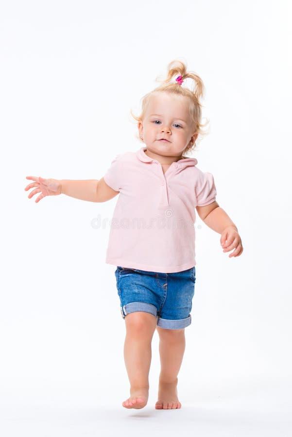 Le bébé mignon de petit enfant apprend à marcher, faire des premières étapes d'isolement sur un fond blanc photo libre de droits