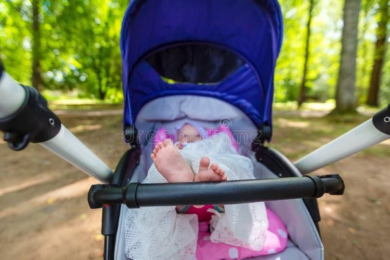 Le bébé mignon de bébé s'assied et voiture d'enfant et a mis ses jambes sur le thehandrail de la poussette de bébé Les parents so images libres de droits