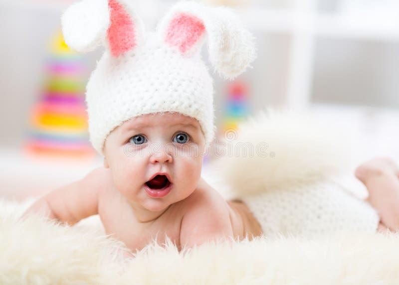 Le bébé mignon de sourire dans le lapin costument le mensonge sur la fourrure dans la crèche photos libres de droits