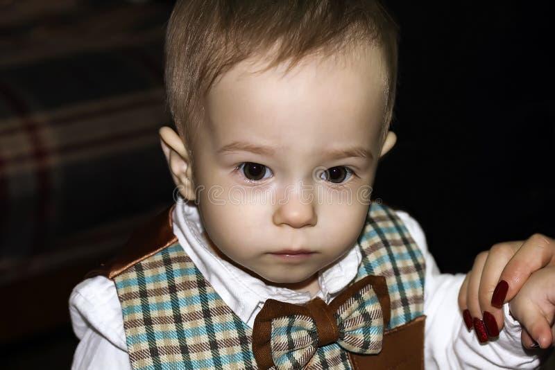 Le bébé mignon sérieux regarde loin Portrait photos stock