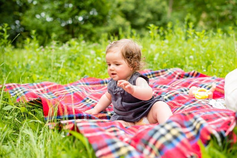 Le bébé mignon s'assied sur une couverture de plaid image stock