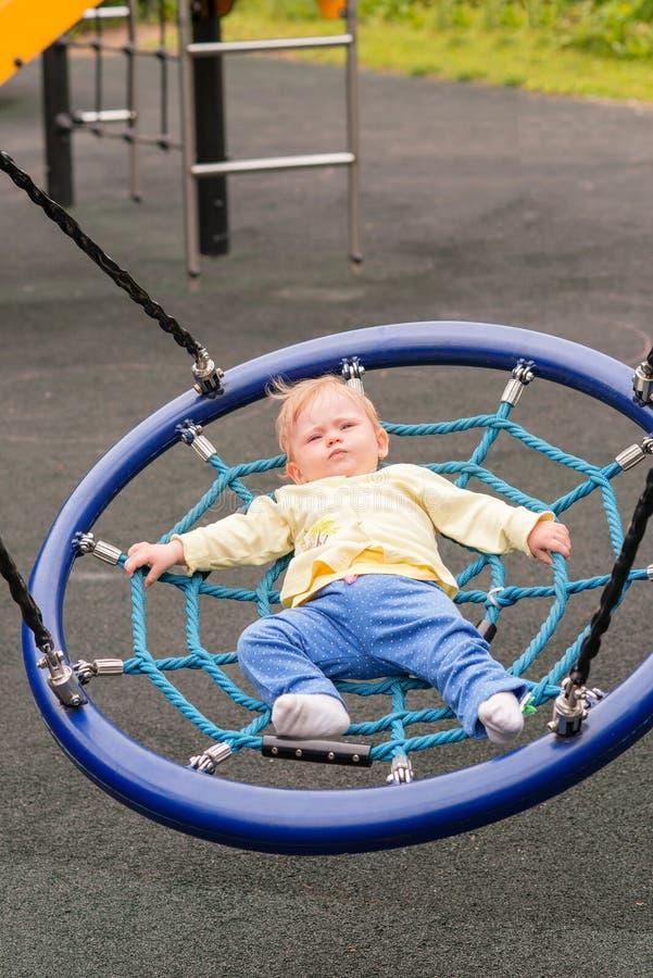 Le bébé monte sur une oscillation photo stock