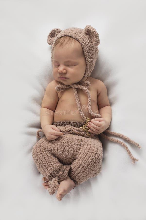 Le bébé nouveau-né dort dans un costume d'ours photos libres de droits