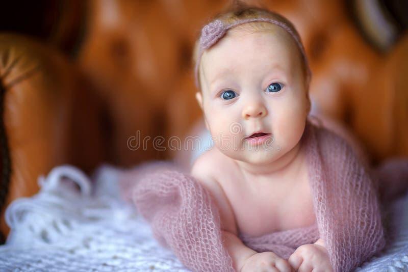 Le bébé nouveau-né heureux se trouve sur une chaise dans un beau chapeau tricoté, avec des regards d'intérêt dans la caméra images libres de droits