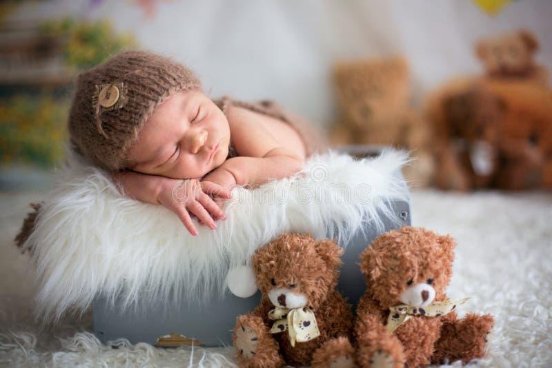 Le bébé nouveau-né mignon dort avec des jouets photos stock