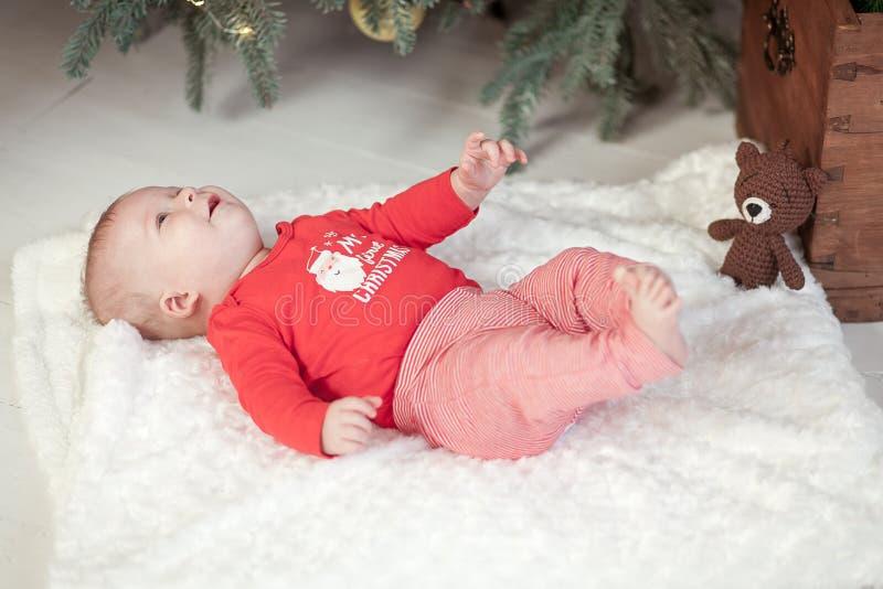 Le bébé nouveau-né mignon se trouve sous l'arbre de Noël sur une ouatine blanche en plan rapproché rouge de pull photographie stock
