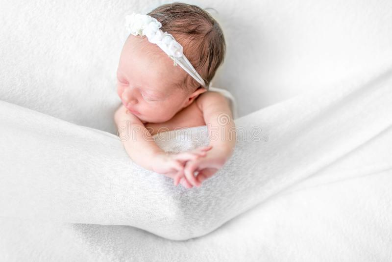 Le bébé nouveau-né se trouvant dessus soutiennent parmi les feuilles blanches images stock