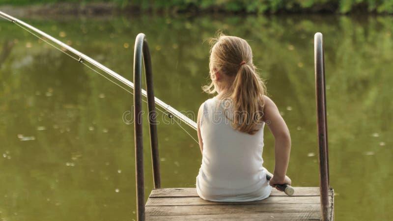 le bébé pêche la fille avec une canne à pêche s'assied sur le rivage photos stock