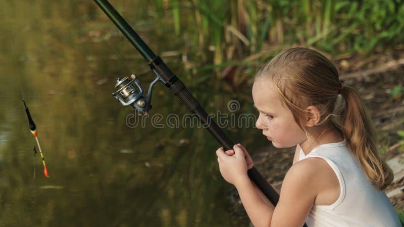 le bébé pêche la fille avec une canne à pêche s'assied sur le rivage image stock