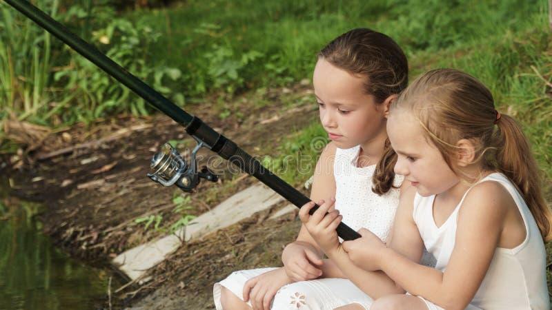 le bébé pêche la fille avec une canne à pêche s'assied sur le rivage photos libres de droits