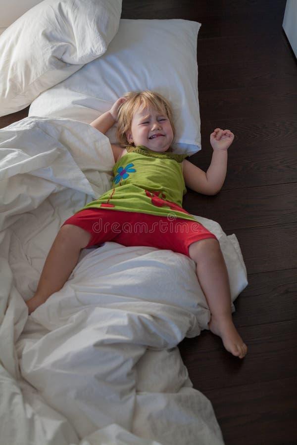 Le bébé pleurant sur le lit vêtx le plancher photos libres de droits