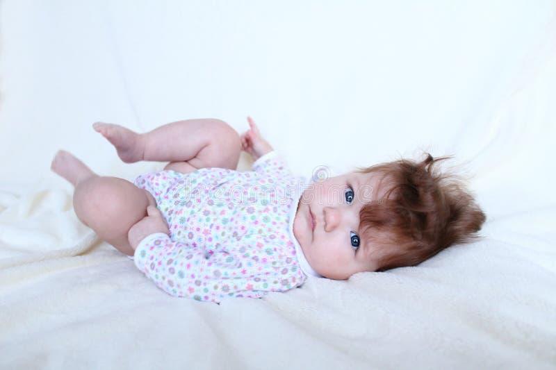 Le bébé sérieux se trouve sur le lit photo stock